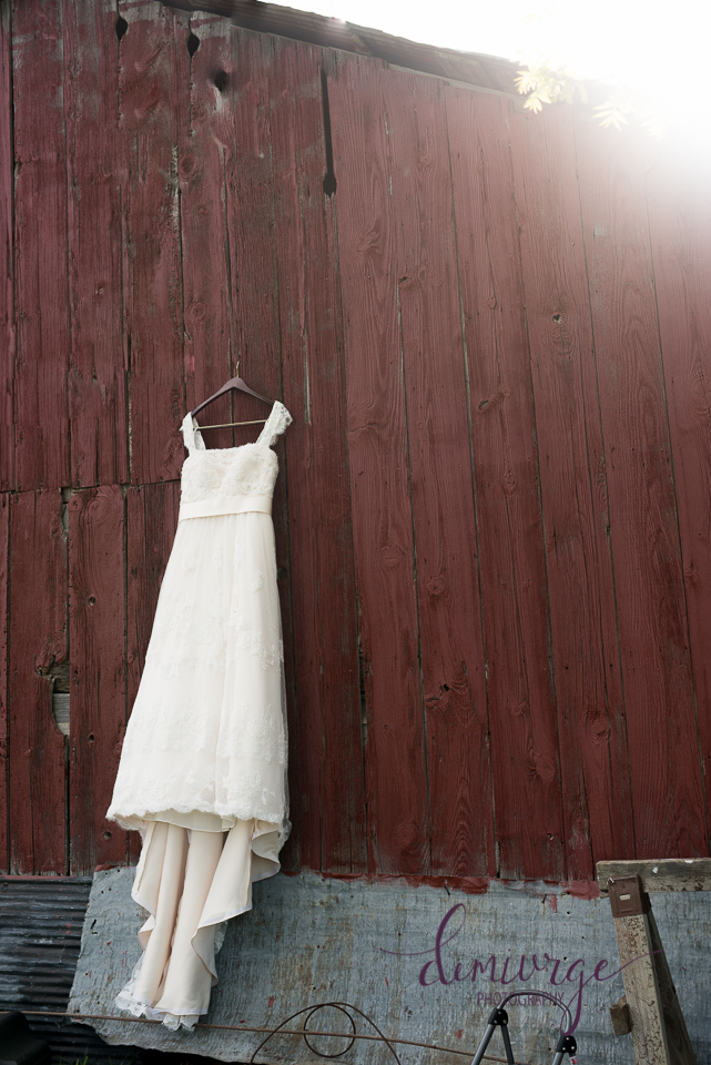wedding dress hanging on barn