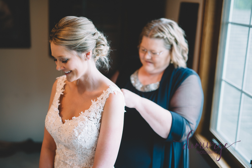 mom helping bride get ready on wedding day