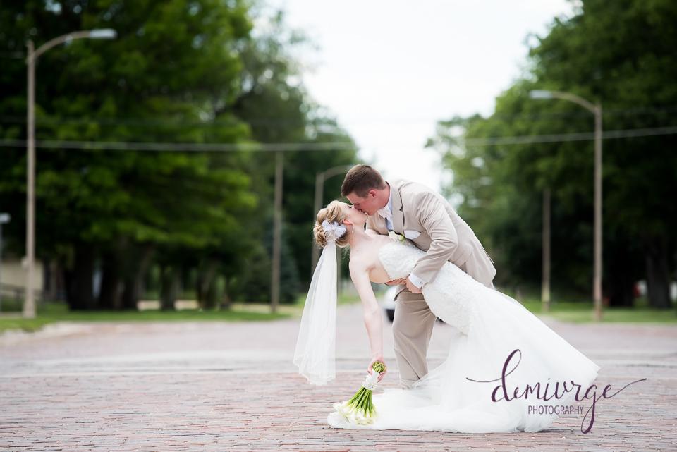 bride and groom dip and kiss on seneca main street